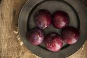Fresh plums in natural light setting with moody vintage retro st — Stock Photo