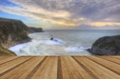 Vibrant sunrise over ocean and sheltered cove with wooden planks — Stockfoto