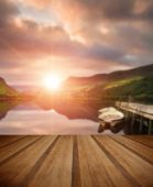 Sunrise over lake with boats moored at jetty with wooden planks  — Stock Photo