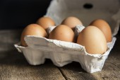 Fresh eggs in egg box in moody natural lighting vintage retro st — Stock Photo