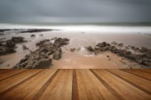 Long exposure landscape beach scene with moody sky with wooden p — Stock Photo
