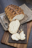 Freshly baked rustic loaf of bread in farmhouse setting with woo — Stock Photo