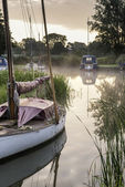 Boats moored on riverbank at sunrise in countryside landscape — Stock Photo