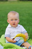 Little boy sits with banana — Stock Photo