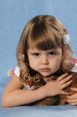 Little girl lying with somali kitten ruddy color — Stock Photo