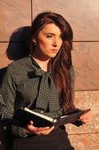 Pretty woman portrait near wall with notepad — Stock Photo