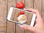 Hands taking photo apple cake with smartphone — Stock Photo