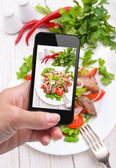 Hands taking photo vegetable salad with meat with smartphone — Stock Photo