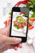 Hands taking photo vegetable salad with meat with smartphone — 图库照片