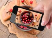 Hands taking photo mulled wine with smartphone. — Stock Photo