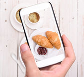 Hands taking photo cup of coffee with croissants with smartphone — Stock Photo