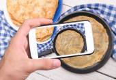 Hands taking photo pancakes with smartphone. — Stock Photo