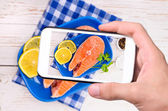 Hands taking photo salmon with smartphone — Stock Photo