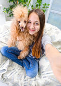 Beautiful girl with dog taken pictures of her self. — Stock Photo
