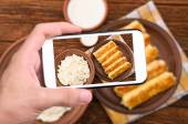 Hands taking photo pancakes with cottage cheese with smartphone. — Stock Photo