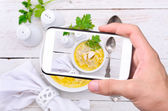 Hands taking photo chicken noodle soup with smartphone. — Stock Photo