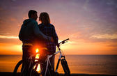 Couple of cyclists at the beach at sunset. — Stock fotografie