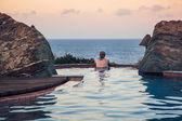 Woman in pool overlooking the sea — Foto de Stock