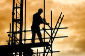 Silhouette construction worker on scaffolding building site — Photo