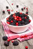 Blackberries and cranberries in a bowl on wooden table — Stock Photo