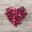Heart from red dry petals on wooden table — Stock Photo #62143895