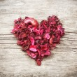 Heart from red dry petals on wooden table — Stock Photo #62143923