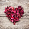 Heart from red dry petals on wooden table — Stock Photo #62144053