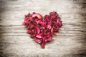 Heart from red dry petals on wooden table — Stock Photo