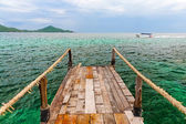 Old wooden pier over the sea shore  — Stock Photo