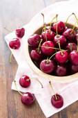 Fresh red cherries in bowl on a wooden table — Stock Photo
