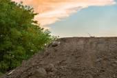 Large pile of soil under blue sky — Stock Photo