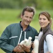 Couple of farmers holding milk bottles — Stock Photo #53237055
