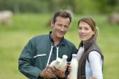 Couple of farmers holding milk bottles — Stock Photo