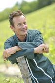 Smiling vinegrower standing in vineyard — Stock Photo