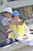 Engineers on building site checking plans — Stock Photo