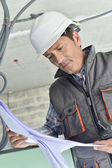 Construction worker checking blueprint — Stock Photo