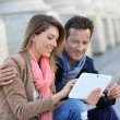 Couple of tourists using digital tablet — Stock Photo #53289177