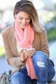 Blond woman using smartphone — Stock Photo