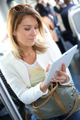 Woman in city train with tablet — Stock Photo