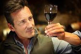 Winegrower holding glass of wine — Stock Photo