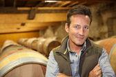 Winemaker standing in wine cellar — Stock Photo