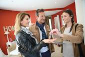 Real estate agent giving keys to clients — Stock Photo