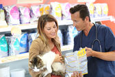 Veterinarian showing pet food to client — Stock Photo