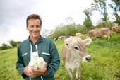 Farmer in field holding bottles of milk — Stock Photo