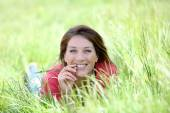 Smiling woman laying in country field — Stock Photo