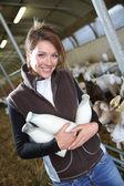 Farmer holding bottles of goat milk — Stock Photo