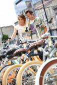 Couple choosing bikes in rental shop — Stock Photo