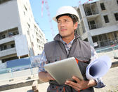 Entrepreneur on building site using tablet — Stock Photo
