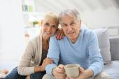 Senior couple sitting on couch — Stock Photo