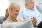 Woman using smartphone, husband reading book — Stock Photo